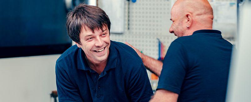 Zwei Männer, Spaß bei der Arbeit, blaue T-Shirts, Schulterklopfen, Lachen, Zerspanungstechnik, Fräsen, Drehen, Industrie