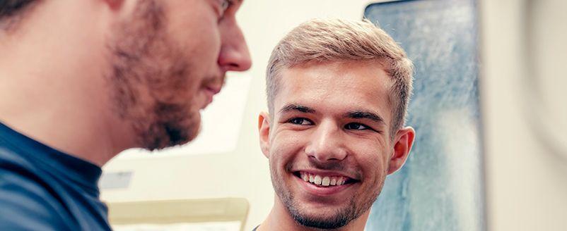 Lächelder junger Mann mit Bart, Industrie, Arbeit, Zerspanungstechnik, Fräsen, Drehen