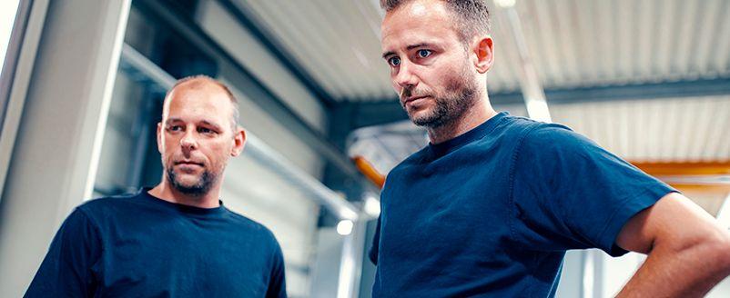 Zwei männliche Mitarbeiter in der Industrie, Blaue T-Shirts, Konzentration bei der Arbeit, Halle