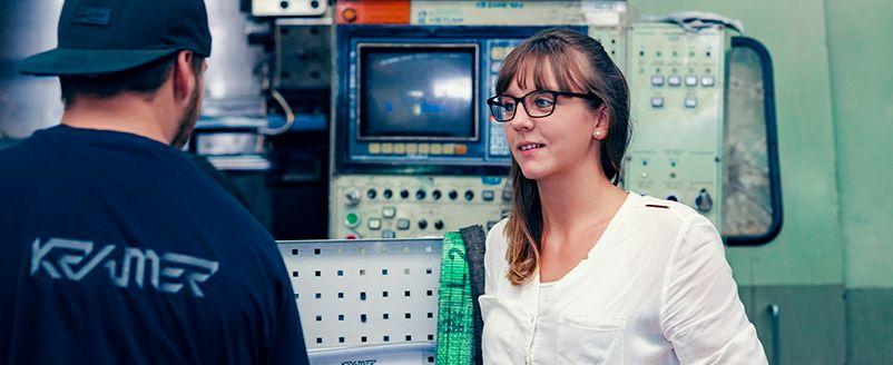 Logo auf blauem T-Shirt, Kappe, Mitarbeiter, junge Frau mit Brille, weißes Obereil, Industrie, grüne Maschine, Zerspanungstechnik, Fräsen, Drehen